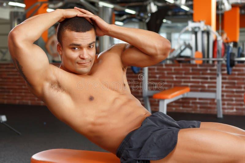 Młody przyjemny mężczyzna robi brzusznym chrupnięciom w gym obrazy stock
