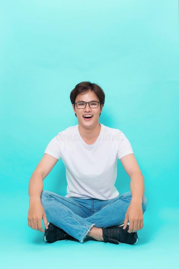 Młody przypadkowy azjatykci mężczyzna obsiadanie na podłoga z jego iść na piechotę crosse zdjęcie stock