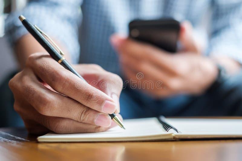 Młody przypadkowy Biznesowy mężczyzna pisze coś na notatniku i używa ekranu sensorowego smartphone w kawiarni biznes, styl życia, obraz royalty free