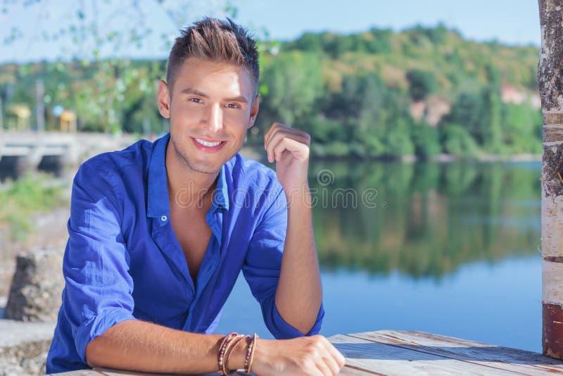 Mężczyzna przy stołowym pobliskim jeziorem fotografia stock