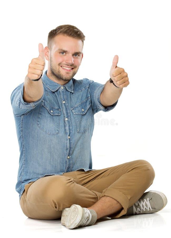 Młody przypadkowy mężczyzna obsiadanie z nogami krzyżować i seans oba thum obrazy stock