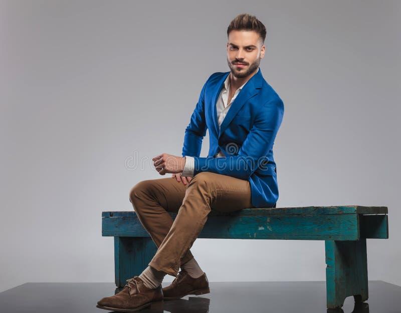 Młody przypadkowy mężczyzna odpoczywa na drewnianej ławce w błękitnym kostiumu zdjęcia royalty free
