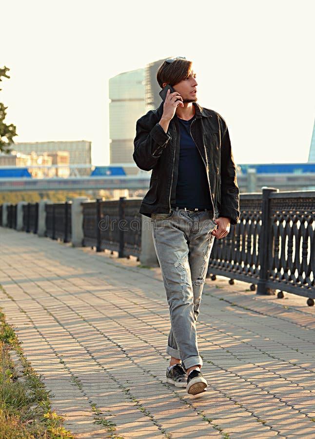 Młody przypadkowy mężczyzna odprowadzenie na ulicie i opowiadać na mobilnym pho fotografia royalty free