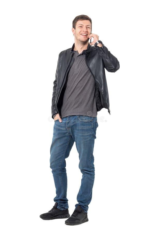 Młody przypadkowy mężczyzna opowiada na telefonie komórkowym roześmianym i patrzeje kamerę obraz stock