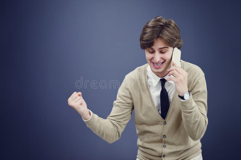 Młody przypadkowy mężczyzna opowiada na telefonie odizolowywającym na białym tle obraz royalty free