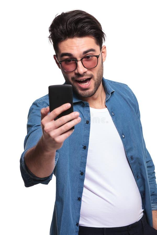 Młody przypadkowy mężczyzna patrzeć szokował przy telefonu ekranem fotografia royalty free