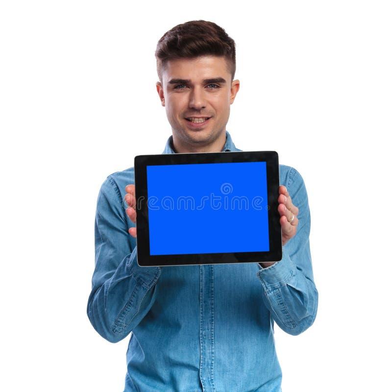 Młody przypadkowy mężczyzna pokazuje pustego ekran pastylka fotografia stock