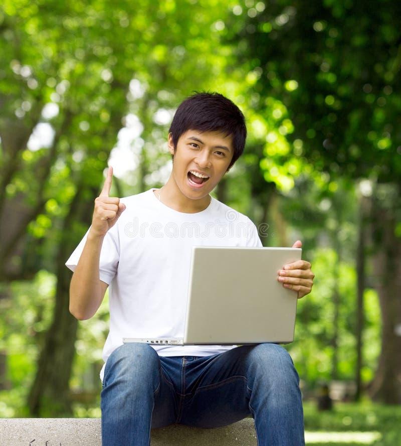 Młody przystojny Azjatycki uczeń z laptopem zdjęcie stock