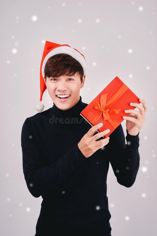 Młody przystojny azjatykci mężczyzna trzyma prezent z Santa kapeluszem, odizolowywającego zdjęcia royalty free