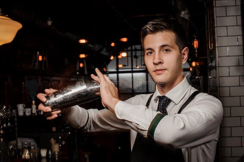 Młody przystojny barman trząść świeżego i smakowitego lato koktajl fotografia royalty free