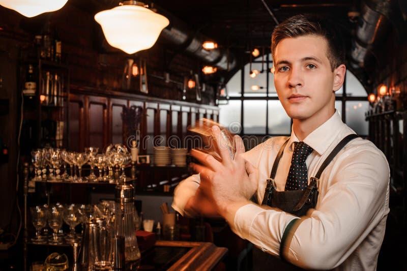 Młody przystojny barman trząść świeżego i smakowitego lato koktajl zdjęcia stock