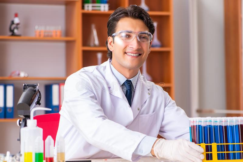 Młody przystojny biochemik pracuje w lab zdjęcia stock