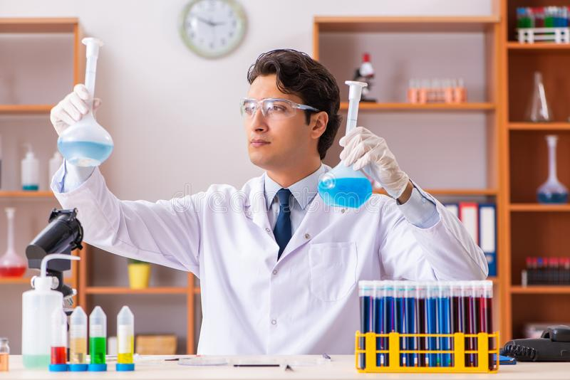 Młody przystojny biochemik pracuje w lab fotografia stock