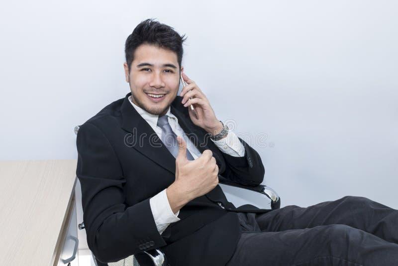 Młody przystojny biznesmen ono uśmiecha się i opowiada z telefonem przy biurem zdjęcia stock