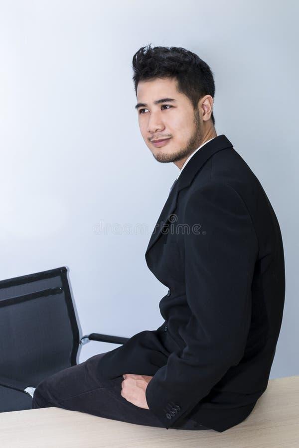Młody przystojny biznesmen uśmiechnięty i mądrze siedzi na stole przy biurem obrazy stock