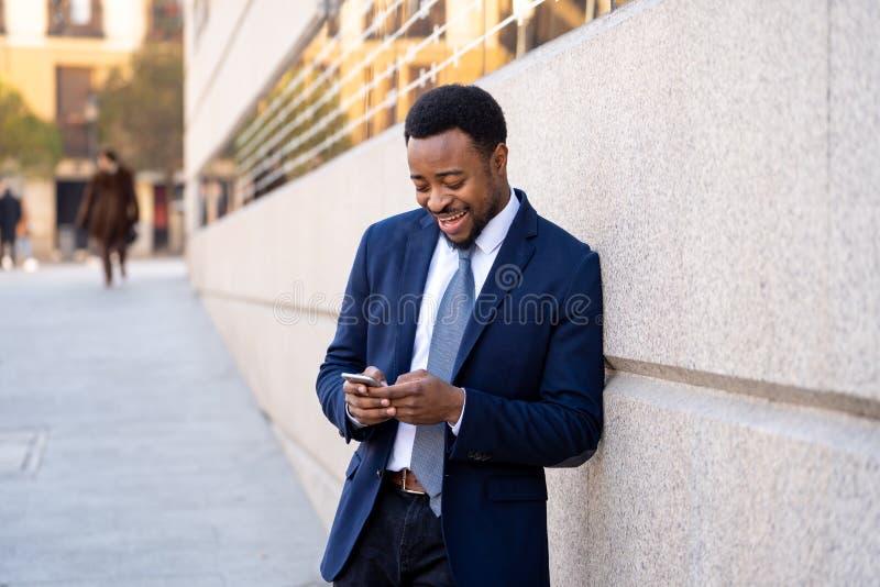 Młody przystojny biznesmen używa telefonu komórkowego app dosłania wiadomość na zewnątrz biura w miastowym mieście obraz stock