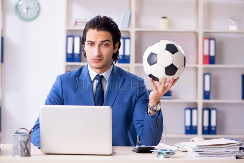 Młody przystojny biznesmen z piłki nożnej piłką w biurze obrazy stock