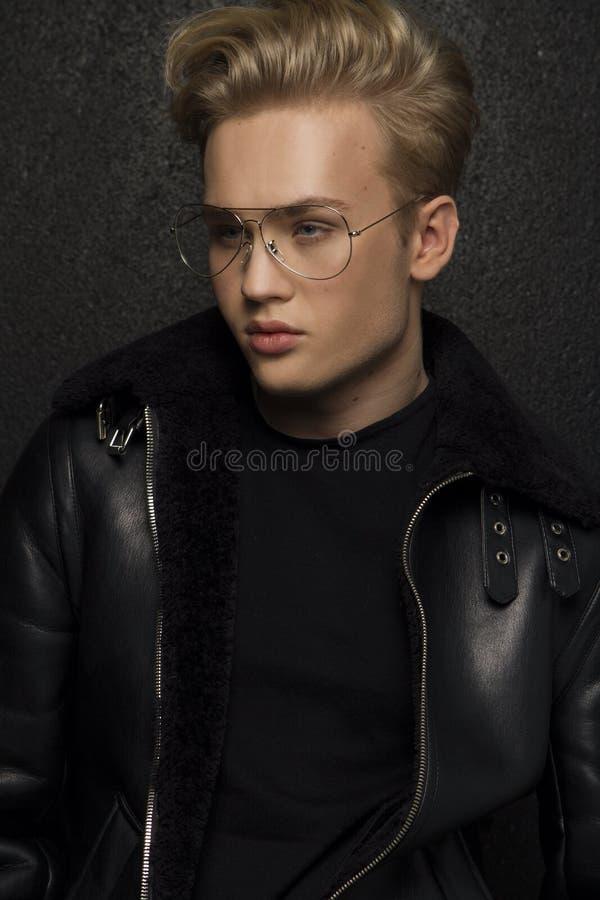 Młody przystojny blond seksowny mężczyzna w skórzanej kurtce i szkłach obraz royalty free