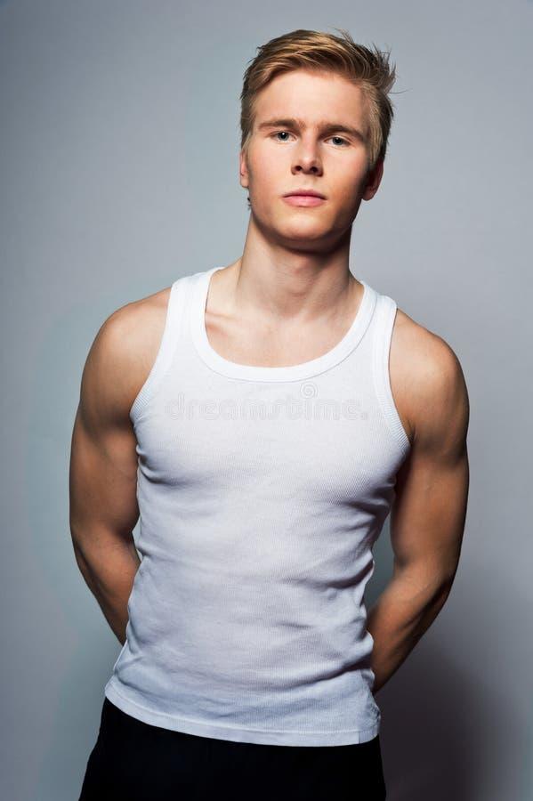 Młody przystojny blondynu mężczyzna jest ubranym koszulkę obraz stock