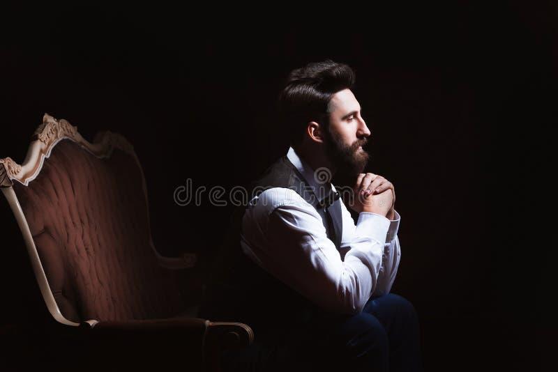 Młody przystojny brodaty caucasian mężczyzna obsiadanie na rocznik kanapie Perfect fryzura i skóra Być ubranym kamizelkę, biała k zdjęcia stock