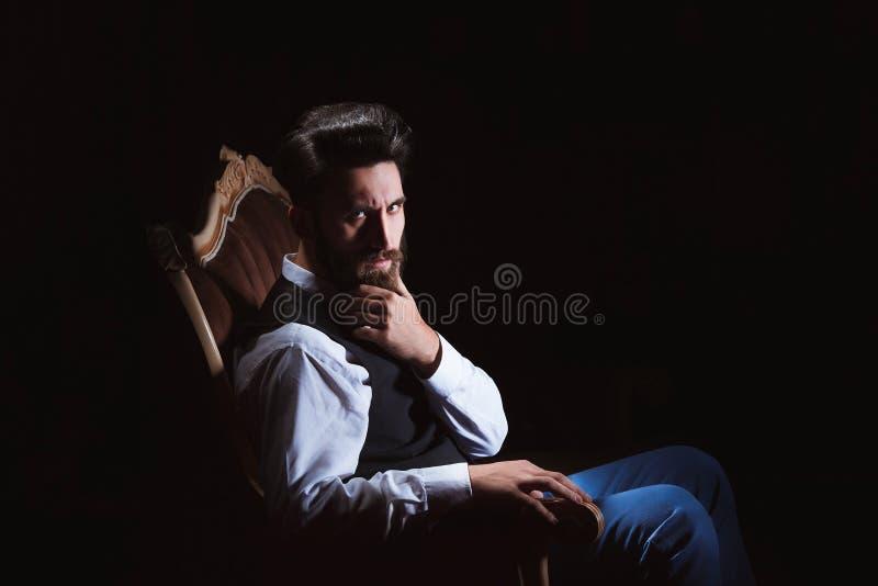 Młody przystojny brodaty caucasian mężczyzna obsiadanie na rocznik kanapie Perfect fryzura i skóra Być ubranym kamizelkę, biała k zdjęcie stock