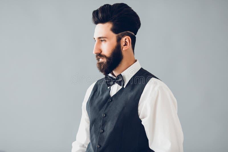 Młody przystojny brodaty caucasian mężczyzna pozuje indoors Perfect fryzura i skóra Być ubranym kamizelkę, biała koszula, cajgi obrazy stock