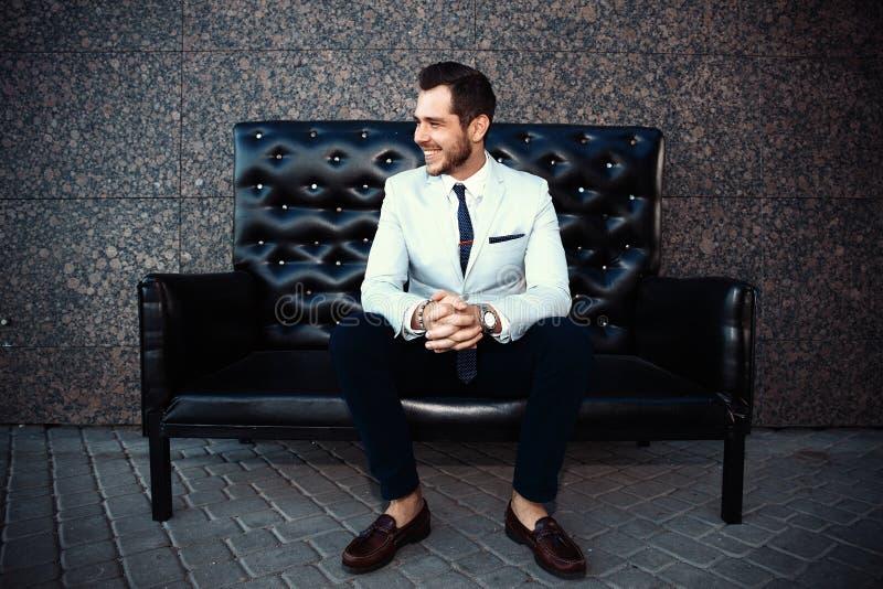 Młody przystojny brodaty elegancki mężczyzna obsiadanie na wygodnej rzemiennej kanapie zdjęcie royalty free