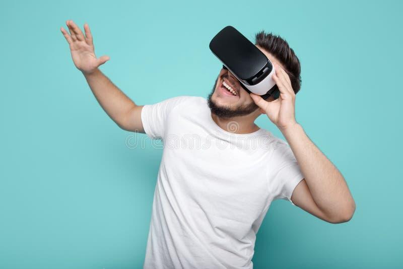 Młody przystojny brodaty mężczyzna jest ubranym rzeczywistość wirtualna gogle w studiu na kolorowym tle Smartphone używać z VR fotografia royalty free