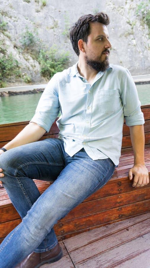 Młody Przystojny Brodaty mężczyzna Siedzi Na Drewnianej łodzi w rzece z cajgami obraz royalty free