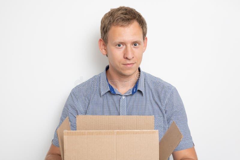 Młody przystojny caucasian mężczyzna trzyma otwartego karton w jego wręcza i ono uśmiechał się fotografia stock