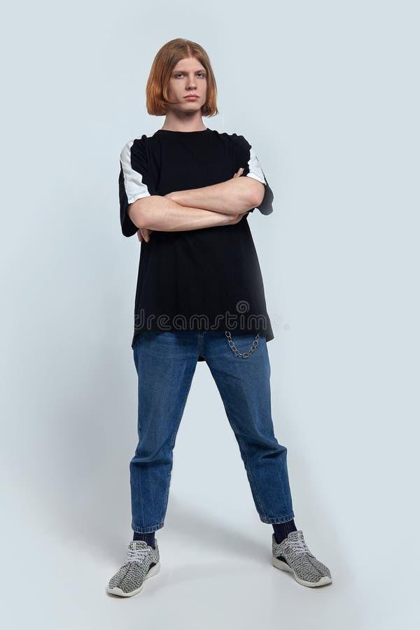 Młody przystojny caucasian mężczyzna z imbirowymi czerwonymi włosów stojakami zbroi skrzyżowanie na lekkim tle zdjęcie stock