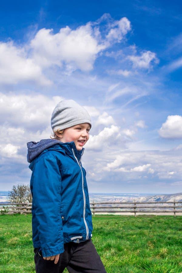 Młody przystojny chłopiec odprowadzenie na zielonej trawie zdjęcie stock