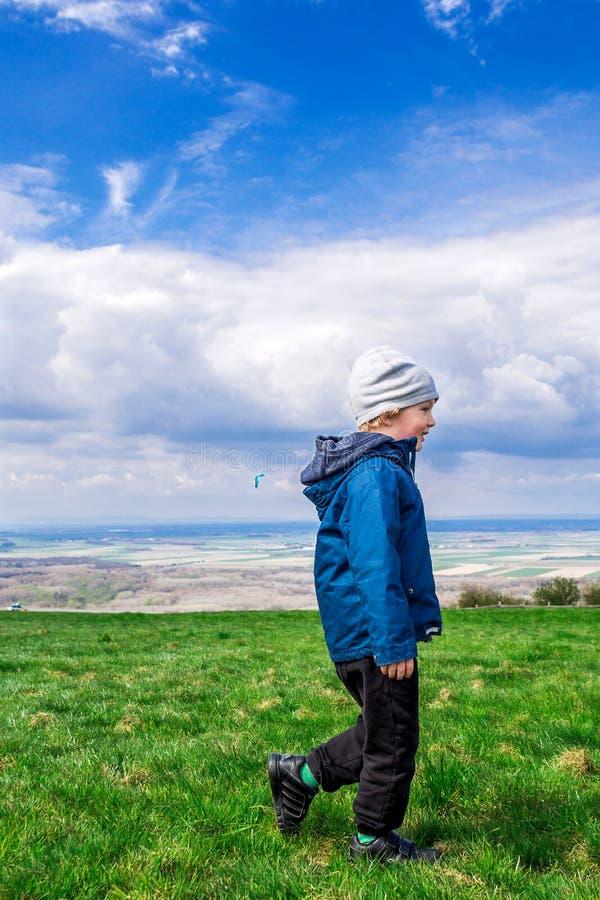 Młody przystojny chłopiec odprowadzenie na zielonej trawie obrazy stock
