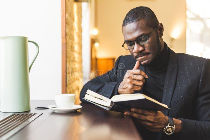 Młody przystojny ciemnoskóry biznesmen w kawiarni czyta książkę z filiżanką herbata obraz stock