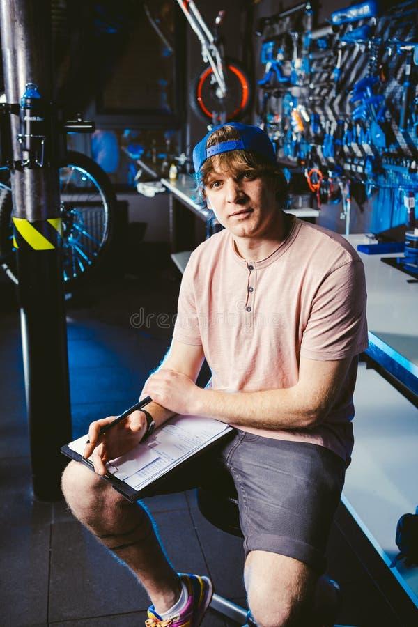 Młody przystojny elegancki mężczyzna w nakrętki snapback z tatuażu małego biznesu właścicielem sprzedaje bicykl i warsztat siedzi obrazy stock