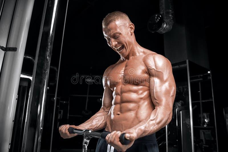 Młody przystojny facet robi ćwiczeniom w gym obrazy stock