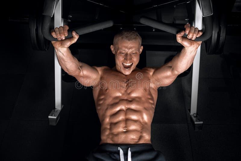 Młody przystojny facet robi ćwiczeniom w gym obrazy royalty free