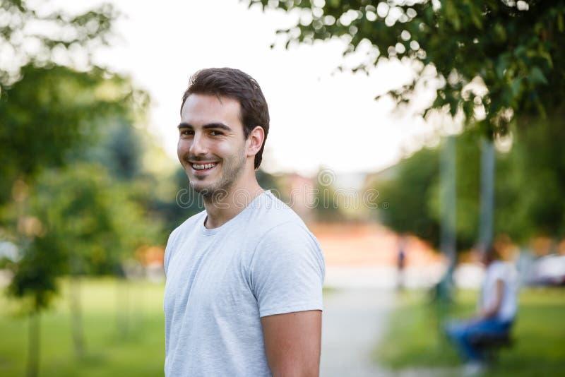 Młody przystojny facet w parkowym standign i ono uśmiecha się obrazy stock