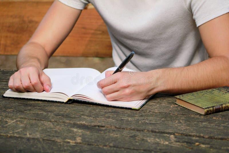 Młody przystojny faceta obsiadanie przy drewnianym stołem, writing książka, robić pracie domowej, bierze notatki, uczenie, kontem zdjęcia stock