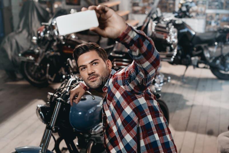 młody przystojny mężczyzna bierze selfie na smartphone z klasycznym motocyklem zdjęcia stock