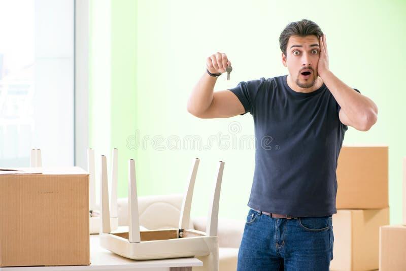 Młody przystojny mężczyzna chodzenie wewnątrz nowy dom z pudełkami zdjęcia royalty free