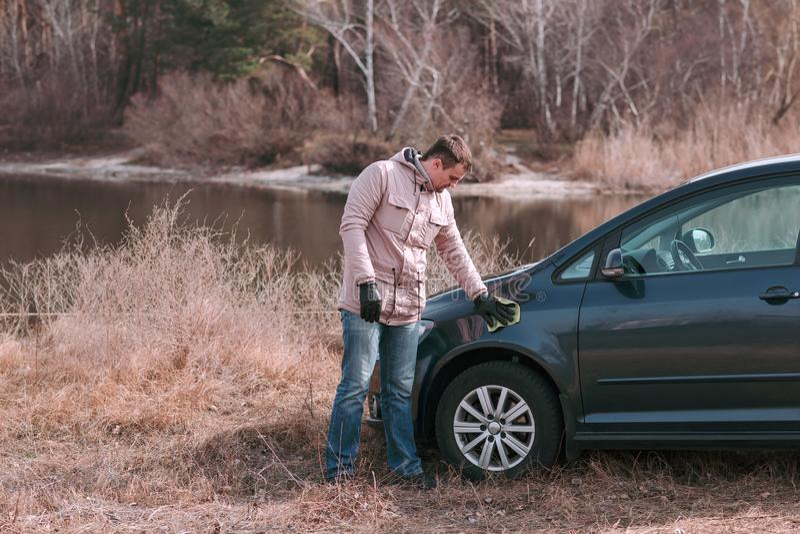 Młody przystojny mężczyzna czyści jego samochód z łachmanem outdoors przed jechać zdjęcie stock