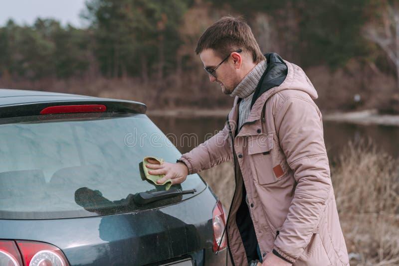 Młody przystojny mężczyzna czyści jego samochód z łachmanem przed jechać zdjęcia stock