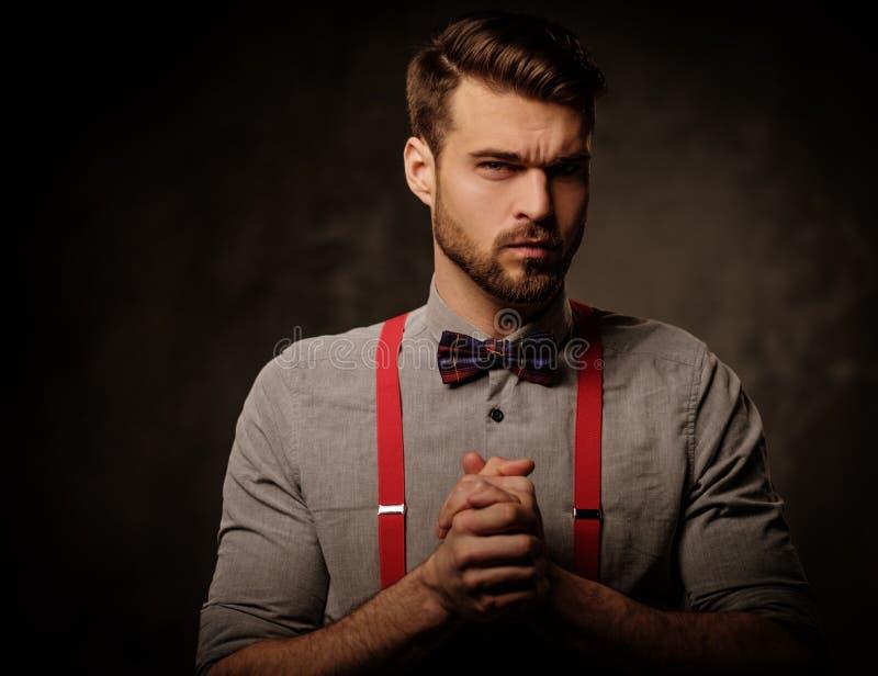Młody przystojny mężczyzna jest ubranym suspenders i łęku krawat pozuje na ciemnym tle z brodą, obrazy royalty free
