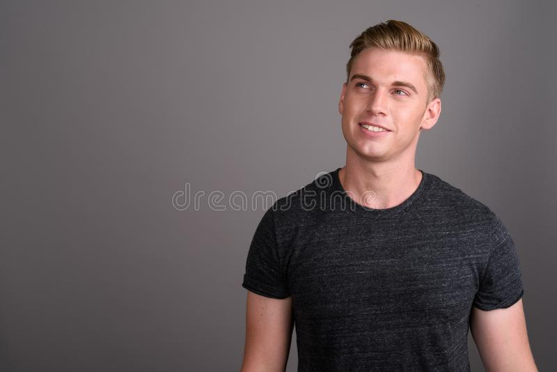 Młody przystojny mężczyzna jest ubranym szarą koszula przeciw gr z blondynem zdjęcia royalty free