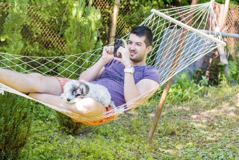 Młody przystojny mężczyzna Relaksuje W hamaku i bawić się z jego telefonem fotografia stock