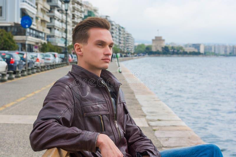 Młody przystojny mężczyzna, turysta, siedzi na nabrzeżu Saloniki, Grecja zdjęcia stock