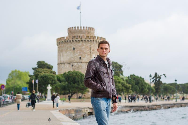 Młody przystojny mężczyzna, turysta, stojaki blisko Biały wierza w centrum Saloniki, Grecja blisko morza zdjęcia royalty free