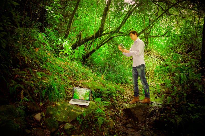 Młody przystojny mężczyzna używa pastylkę i laptop z obrazy royalty free