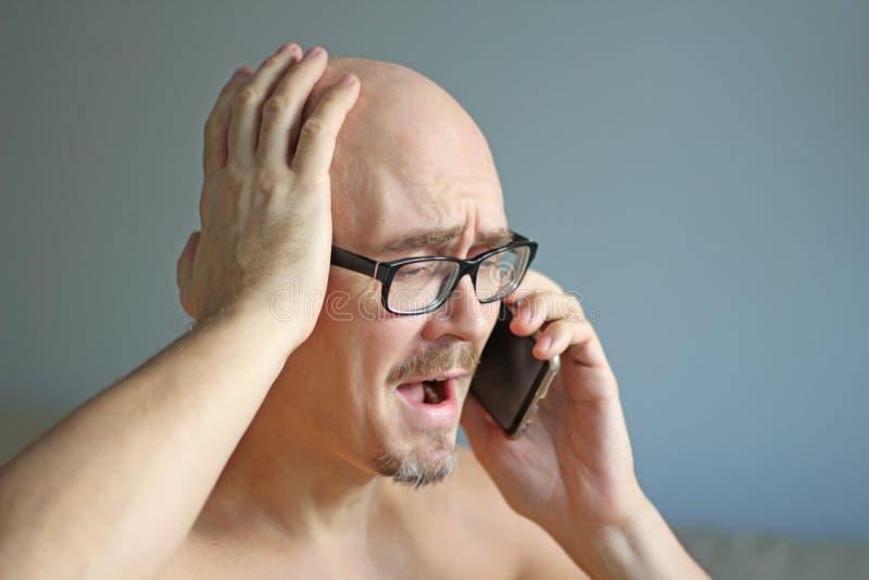Młody przystojny mężczyzna w czarnych szkłach opowiada na telefonie Duzi problemy, skandal, zła wiadomość zbliżenie odizolowywają obraz royalty free